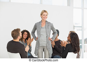 Rehab group applauding woman standing up at therapy session