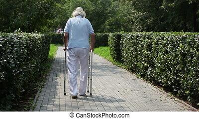 Back-view of a senior man taking first steps after bed regime