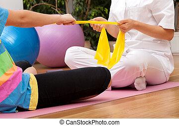 Rehabilitation exercises - Phystiotherapist exercising with ...