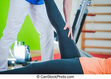 Rehabilitation Physiotherapy. Caucasian Therapist Working...