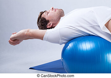 Man is stretching on fitness ball to care about his spine