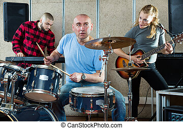 Rehearsal of music group with male drummer