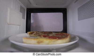 Reheating leftover pizza in the microwave. Young girl opens the door and takes out slice of heated pizza. View through the oven.