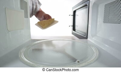 Reheating leftover slice of cheese pie on styrofoam tray in the microwave oven