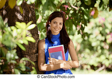 reihenfolge, von, studenten, porträt, an, schule, glücklich, junge frau, lächeln, mit, hochschule, lehrbücher, park, lehnen, baum