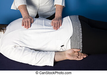 A young woman is getting a reiki treatment