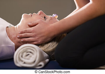 Reiki therapy with girl working as spirit healer, arranging crystals and gemstones on female client for treatment