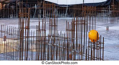 Reinforced concrete, under construction. Columns steel bars reinforcement and yellow hardhats