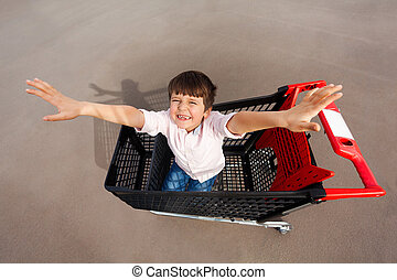 reizend, junge, spaß haben, und, spielende , mit, einkaufswagen