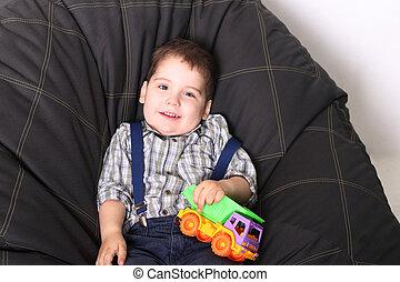reizend, kleiner junge, sitzen, auf, weich, tasche, mit, kugel, und, hält, kinderauto, in, studio