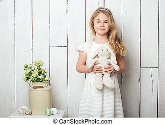 reizend, kleines mädchen, mit, a, kaninchenkaninchen, spielzeug, weiß, holz, hintergrund