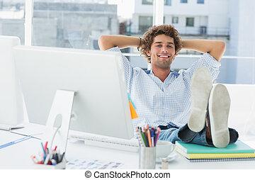 relajado, casual, hombre, con, piernas, en el escritorio, en, brillante, oficina