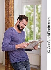 relajado, hombre estar de pie, leer un periódico