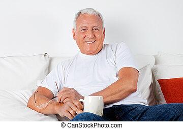 relajado, hombre mayor, teniendo, con, tibio, bebida