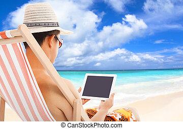 relajado, hombre que sienta, en, sillas de playa, y, conmovedor, tableta