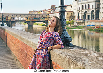 relajado, mujer joven, en, terraplén, cerca, ponte vecchio, en, florencia