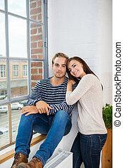 relajado, pareja joven, sentado, en, fuente, de, un, ventana
