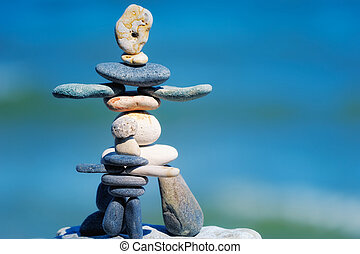 Balance of pebble as figurines on the background the sky