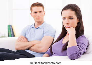 Relationship breakdown. Depressed young woman holding hand on chin and looking away while man sitting behind her on the couch and keeping arms crossed