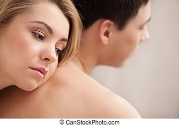 Relationship difficulties. Young depressed woman leaning at her boyfriend back and looking away