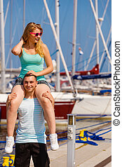 Man giving girlfriend piggyback ride on marina