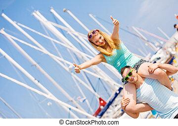 Man giving girlfriend piggyback ride on marina