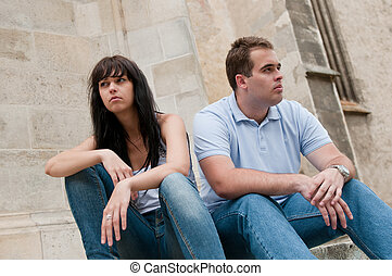 Relationship problems - Young couple sitting outdoors on ...