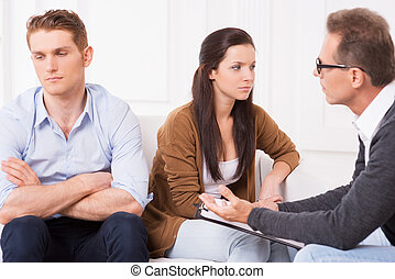 Relationship troubles. Displeased young couple sitting on the couch and looking away while psychiatrist talking to them and gesturing