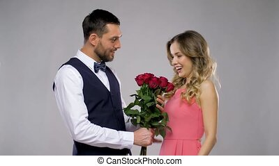 happy man giving flowers to woman - relationships and people...
