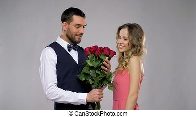 happy man giving flowers to woman