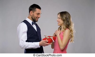 happy man giving present in gift box to woman -...