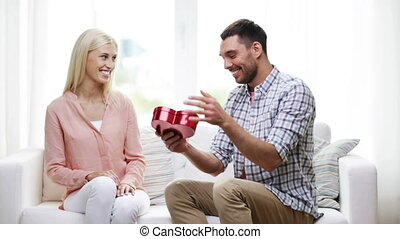 man giving woman red heart shaped gift box