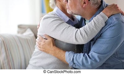 happy senior couple hugging at home - relationships, old age...