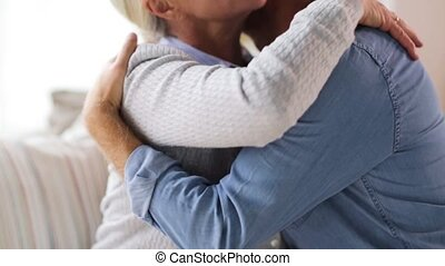 happy senior couple hugging at home