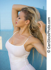 relax, beautiful blonde woman in white shirt posing on a terrace set beside the sea in summer, Spain