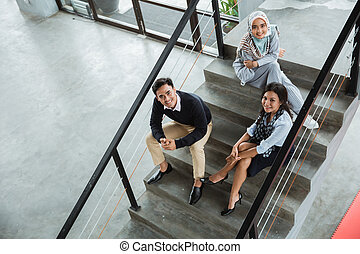 business people chatting in the office staircase