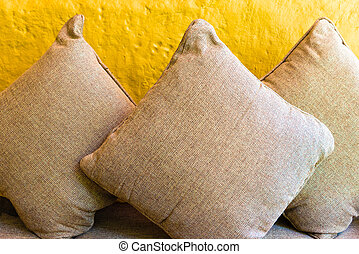 Relax cushion pillows on sofa against yellow background wall
