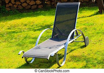 Relax. Empty deck chair on grass in garden.