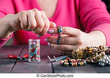 Relax hobby. Female make craft beads
