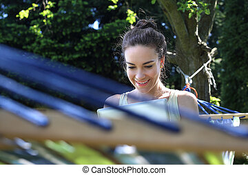 Relax in the sun. Young woman resting on a hammock