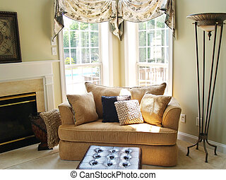 Large chair and footstool brightly lit by the sun streaming in two windows in a luxury home
