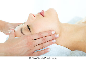 Photo of masseuse�s hands doing relaxing massage on young woman's face