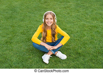 relax on green grass. spring leisure time. happy childhood. kid in headset. happy little girl listen favorite song. kid beauty and fashion. teen girl listen music outdoor. sounds of nature