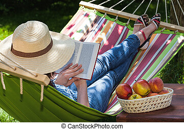 Relax on hammock - A woman relaxing on a hammock with a...