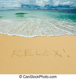 relax written in a sandy tropical beach