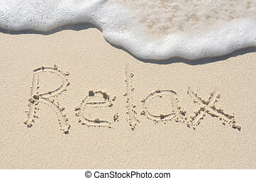 The Word Relax Written in the Sand on a Beach