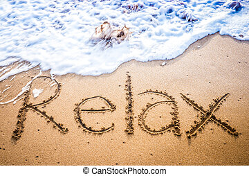 The word RELAX written into the sand on a tropical sandy beach in paradise. The waves are just about to wash the word away.