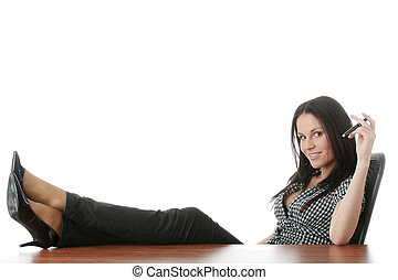 Relax - Young businesswoman relaxing at the desk, legs up, ...