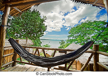 Relaxation - Hammock with ocean in background in coastal...