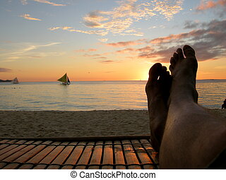 Relaxation - Relaxing on a beach chair at sunset.